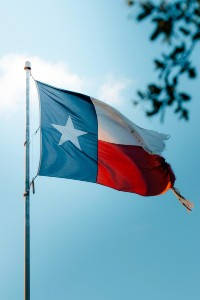 image of Texas flag flying on a sunny day